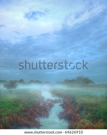 Beautiful English countryside Autumn Fall landscape with stream and mist in morning