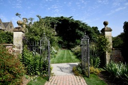 Beautiful English parks and gardens in summer time . English countryside.  Walk ways and green lawns , beautiful rough iron gates and gate posts. A sun dail and flowers , hedges and trees.