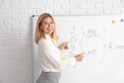 Beautiful English teacher near board in classroom