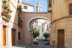 Beautiful entrance decorated with its pots of geraniums on the balconies to the Plaza de Bocairent, province of Valencia, Valencian Autonomous Community, Spain