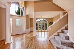 Beautiful entrance hall with high ceiling, columns and arch window in luxury house.