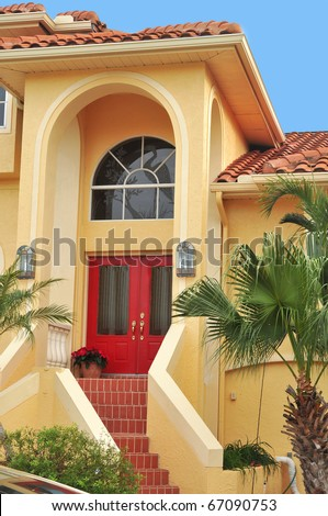 Beautiful entrance to a large, elegant three story home in lush Tropical Florida seated on a waterfront canal. Palms and bushes flank the tiled stairs leading to the double doorway.