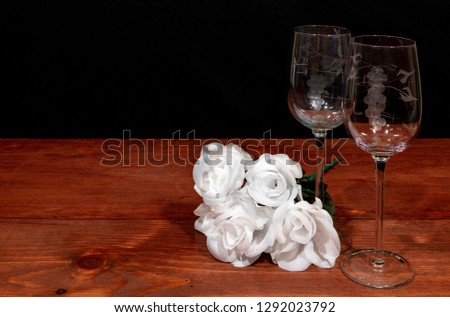 Beautiful etched wine glasses with awhite roses on wooden table and dark background. Valentines, Mothers Day, Easter, Christmas, Wedding Concepts #1292023792