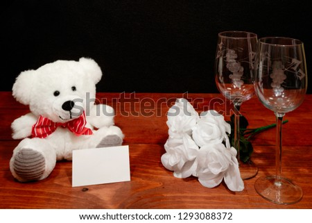 Beautiful etched wine glasses with bouquet of white roses and white teddy bear and card on wooden table and dark background. Valentines, Mothers Day, Easter, Christmas, Wedding Concepts #1293088372