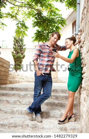 Beautiful ethnically diverse tourist couple visiting monument on cultural vacation trip sightseeing, using smartphone networking together outdoors. Travel technology leisure recreation lifestyle.