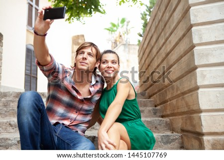 Beautiful ethnically diverse tourist sitting, heads together with stone walls on holiday sightseeing, using smartphone taking selfies photos, outdoors. Travel technology leisure recreation lifestyle.