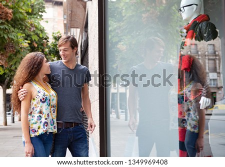 Beautiful ethnically diverse young tourist couple looking at clothing in shopping street store window with manikins, smiling together outdoors. Man and woman consumers, leisure recreation lifestyle.