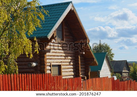 Beautiful ethno wooden house. Summer landscape with a lonely house. Houses in the village.