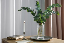 Beautiful eucalyptus branches, old book and holder with burning candle on wooden table indoors. Interior element