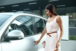 Beautiful european girl open door of her private automobile. Serious young brunette woman wear white dress and hold car key and handbag. Concept of modern woman. City daytime