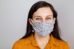 beautiful European girl with blue eyes in a handmade mask from the coronavirus. Design work protecting the security of disinfection of quarantine. Lack face cover. Pandemic houses white background