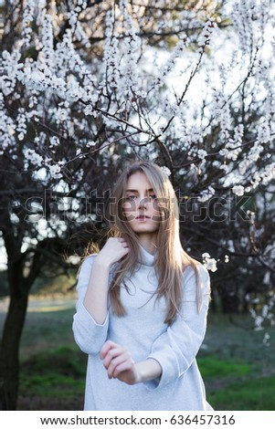 Beautiful european  model touches her hair and posing on camera. Pretty young woman stands in park on blossom trees background. Dressed in white sweater. She looking at camera. Tight medium shot.