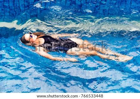 Beautiful european woman is relaxing near the swimming pool