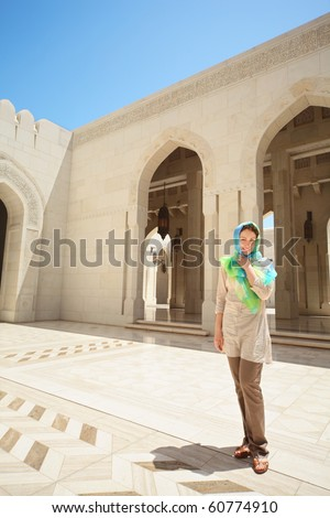 beautiful european woman with kerchief on her head in arab country. she is inside Grand Mosque in Oman.