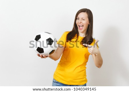 Beautiful European young cheerful happy woman, football fan or player in yellow uniform pointing on soccer ball isolated on white background. Sport, play football, health, healthy lifestyle concept