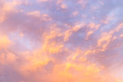 Beautiful evening cloudy sky with a small illuminated area. Pink warm clouds at sunset. Colorful background of evening clouds