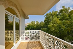 Beautiful Evening shot of the Balcony with White Ornamental Railings with Green Trees around