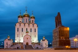 Beautiful evening view of the great cathedral. The Cathedral of the Holy Trinity and the monument to Saint Innocent of Moscow in the city of Magadan. Russian Orthodox Church in the Far East of Russia.