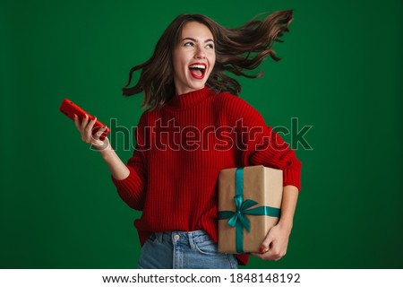 Beautiful excited girl screaming while posing with Christmas gift and cellphone isolated over green background