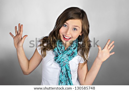 Beautiful excited teenage girl with hands up. Smiling and looking into the camera