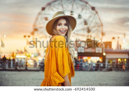 Beautiful exited smiling tourist woman having fun at amusement park at hot summer day trip on the beach. #692414500