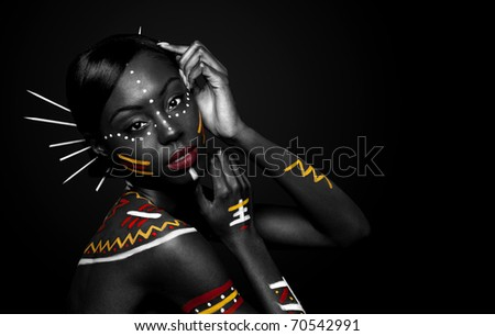 Beautiful exotic African female fashion face with tribal yellow red and white makeup cosmetics and sticks in hair.