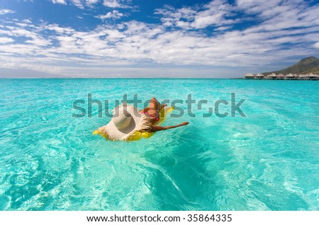 beautiful exotic woman with yellow inflatable raft in turquoise waters near tropical resort