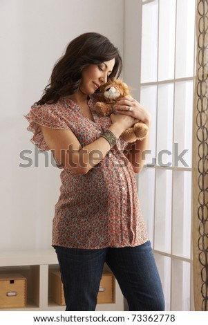 Beautiful expecting mother at six months pregnant holding stuffed animal toy on belly in anticipation of playing with her baby.