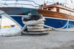 beautiful expensive yacht is tied with a rope to a metal bollard in the port. sea ship is standing in a dock. Close-up of the cable and metal anchor. Insurance concept. Travel at sea