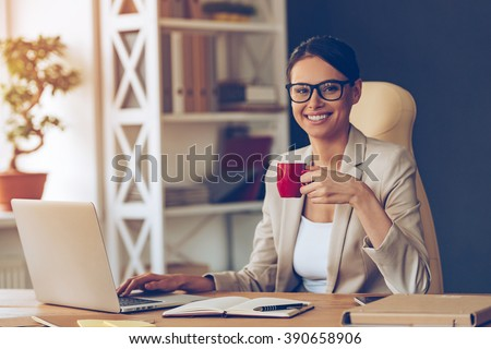 Beautiful expertise. Cheerful young beautiful businesswoman in glasses holding coffee cup and looking at camera with smile while sitting at her working place