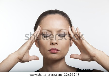 beautiful expressing woman portrait on isolated background massaging her head