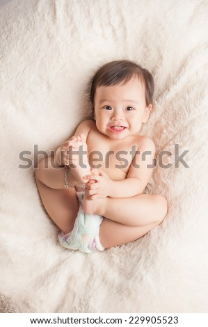 Beautiful expressive adorable happy cute laughing smiling asian baby infant face showing tongue, isolated.