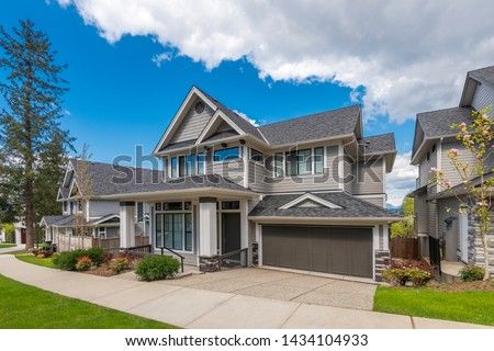 Beautiful exterior of newly built luxury home. Yard with green grass and landscape. #1434104933