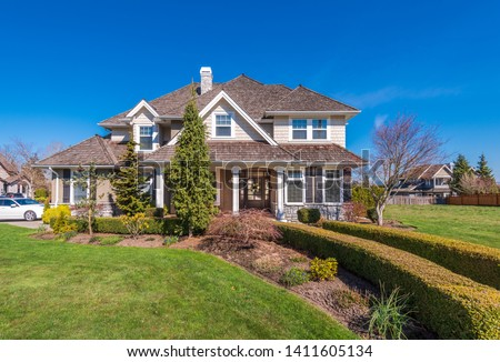 Beautiful exterior of newly built luxury home. Yard with green grass and nice landscape.