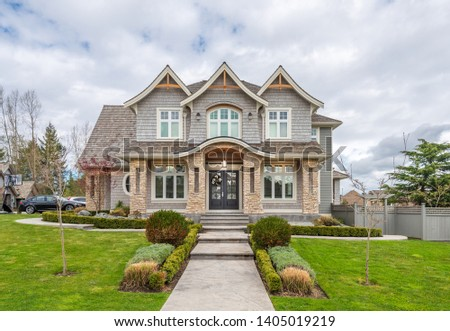 Beautiful exterior of newly built luxury home. Yard with green grass and stones. #1405019219