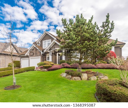 Beautiful exterior of newly built luxury home. Yard with green grass and walkway lead to front entrance. #1368395087