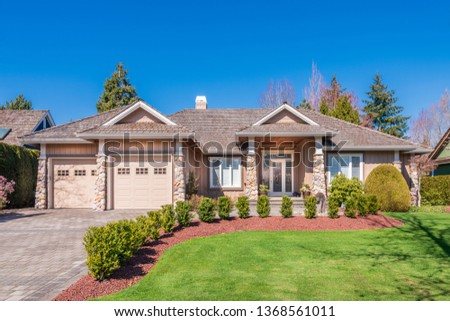Beautiful exterior of newly built luxury home. Yard with green grass and walkway lead to front entrance. #1368561011
