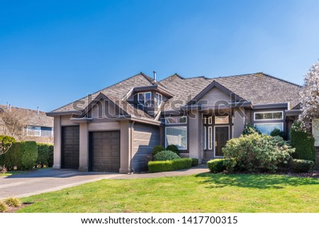 Beautiful exterior of newly built luxury home. Yard with green grass and walkway lead to front entrance. #1417700315