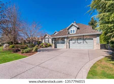 Beautiful exterior of newly built luxury home. Yard with green grass and walkway lead to ornately designed covered porch and front entrance. #1357796015
