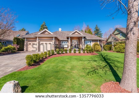 Beautiful exterior of newly built luxury home. Yard with green grass and walkway lead to ornately designed covered porch and front entrance. #1357796033