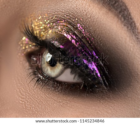 Beautiful Eye Make-up with colorful sparks. Beauty bright fashion holiday smoky eye makeup. Make up sample, close-up of model woman green color eye. Purple and golden glitter eyeshadows