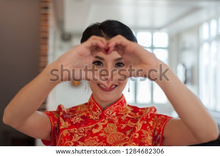 Beautiful eyes. The beautiful eyes of a beautiful girl who looks through her hands that make a heart-shaped symbol. Happy Chinese New Year Festival.