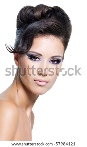 Beautiful face of a glamour woman with modern curly hairstyle and colored makeup - stock photo