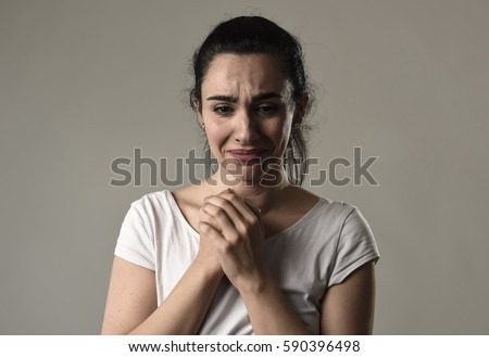 beautiful face of sad woman crying desperate and depressed with tears on her eyes suffering pain and depression isolated on grey background in sadness facial expression and emotion concept #590396498