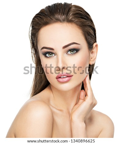 Beautiful face of the young beautiful woman - isolated on white. Gorgeous female portrait with slicked brown hair. Young adult girl with healthy skin. Pretty lady with fashion eye makeup.