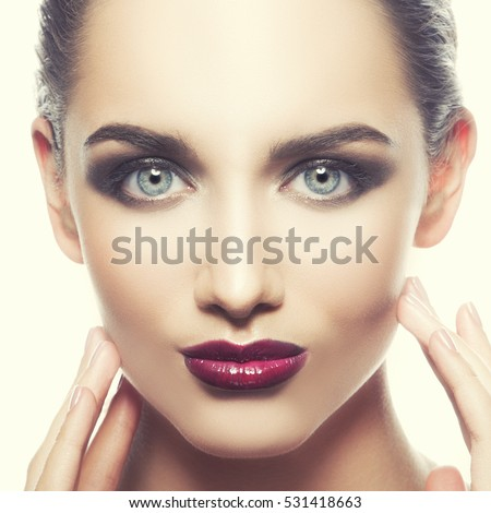 Beautiful face of young caucasian brunette woman with red glossy lips, intensive make-up, perfect skin and blue eyes isolated on white touch her skin. Studio portrait. Toned #531418663