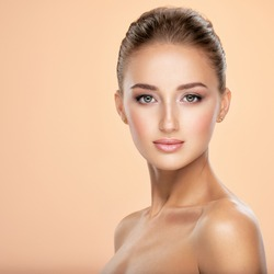 Beautiful face of young caucasian woman with health fresh skin  -  on colored background.  Beauty face concept. Young attractive girl with a healthy skin of  face posing in front of camera.