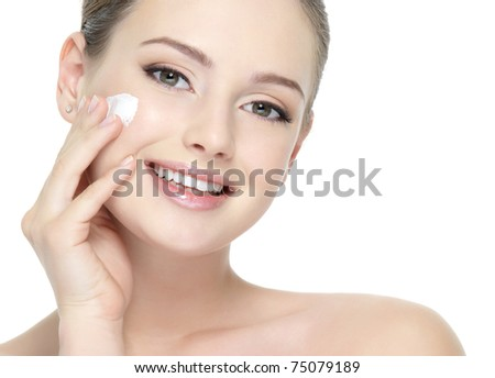 Beautiful face of young smiling woman applying cream on the cheek - white background