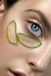 Beautiful face of young woman with pieces of aloe vera plant on her clean perfect skin. Model with aloe vera natural organic patches for SPA, wellness and skincare concept. Close up, selective focus.