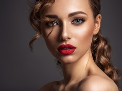 Beautiful face of young woman with red lipstick. Portrait of a stunning sexy girl looks at camera. Attractive model with stylish makeup.  Closeup portrait of a caucasian female.